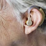 The side of a deaf person's head, showing an ear with a hearing aid